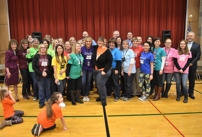 Winning teacher Lisa Richard, center in purple, is surrounded by the entire staff of Pioneer School, stretched between Milken Family Foundation executive Jane Foley at left and Oregon schools chief Salam Noor at far right. Pioneer is a K-6 Title I school about 90 minutes south of Portland.