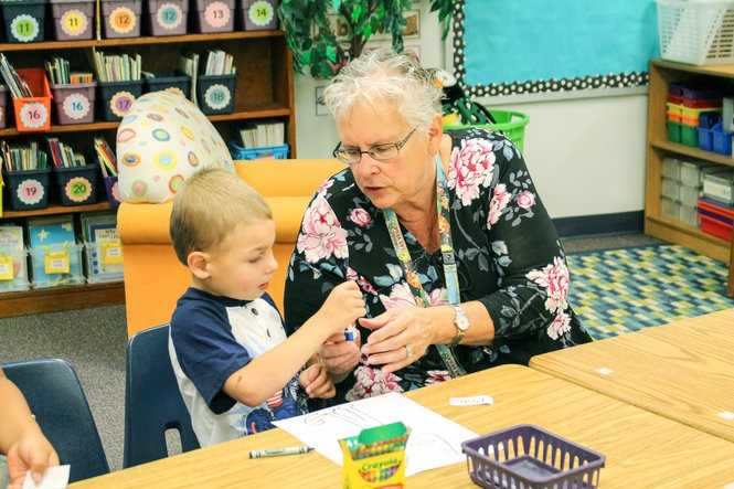 """Teacher Robin McClendon helps Rylen Bates during an August """"camp"""" designed to help McMinnville students about to start kindergarten meet their teachers and learn school routines. All McMinnville teachers are expected to know a dozen or so agreed-upon strategies that research has shown deliver big payoffs for student learning."""