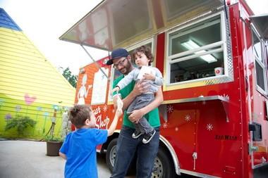 Dustin Micheletti and his sons, Jasper and Aram, play outside the Sugar Shop, a Northeast Portland dessert cart.