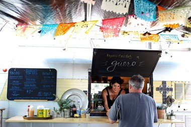 Megan Sanchez, co-owner of the 3-month-old Guero taco and torta food cart, hands a customer his order.