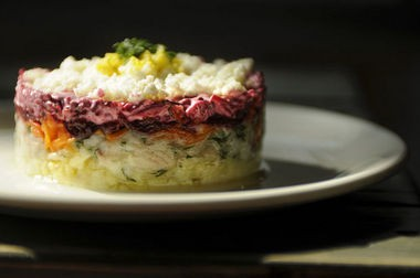 """Kachka's """"herring under a fur coat,"""" with salted herring, potato, carrot, onion, beet, mayo and a dusting of egg white and yolk."""
