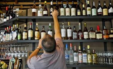 Randy Goodman, one of the proprietors of Bar Avignon pulls down a bottle of wine off the shelf.