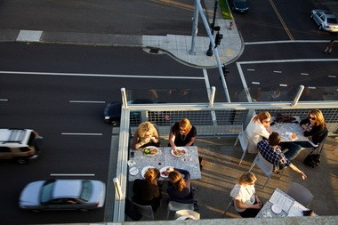 The outdoor seating at Noble Rot hangs right over Burnside.