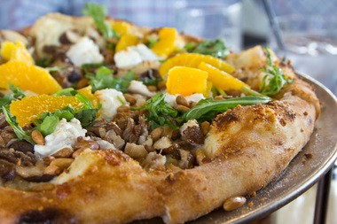 Mt. Tabor Brewing's decadent and challenging Survivor pizza, with duck confit, local mushrooms, chevre, arugula, orange, toasted pine nuts, and parsnip puree.