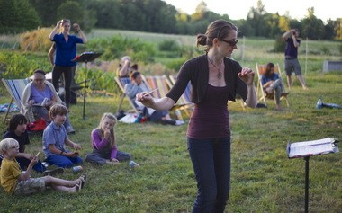 """Erica Melton, Opera Theater Oregon's artistic director, conducts a rehearsal of """"The Cunning Little Vixen"""" as the summer sun sets on Wild Goose Farm, Sauvie lsland."""