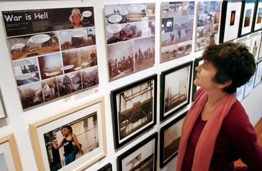 """During a visit home in 2005, Portland-born filmmaker Penny Allen, who now lives in Paris, looks at a local gallery installation of """"War is Hell,"""" a piece of her work that shows frames from video shot in Iraq with added dialog, much like that of a graphic novel."""