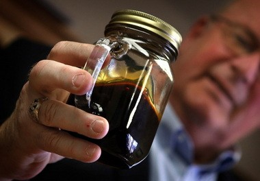Ward Koeser, may of Williston, N.D., holds a jar of crude oil extracted with fracking technology from the stateâs oil fields. Crude oil from North Dakota is being shipped to the Northwest. In Clatskanie along the Columbia River, the oil is being stored in one-time ethanol storage tanks before being shipped to West Coast refineries.