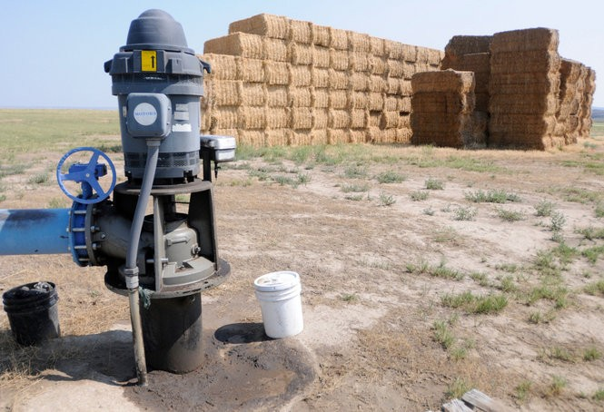 A high-powered wellhead stands sentinel near stacked hay bales in Harney County.