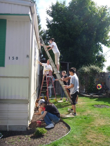 By adopting a graduation requirement that students engage in community service, such as this work party at a local residence, Pacific University officials believe they are developing well-rounded individuals who understand how their skills and career interests fit into the larger society.