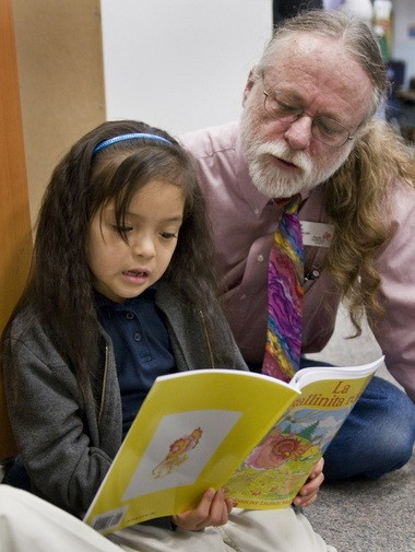Cornelius Elementary kindergartner Arisbeth Vigil reads with Pacific University professor Mark Bailey from the book she selected to keep Monday, March 18, during what was believed to be the last book distribution at the school. After community members stepped in to help, the program will keep going for at least the next few years.