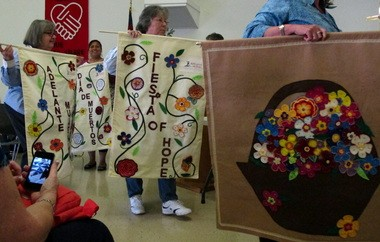 Members and volunteers from Adelante Mujeres showed off the product of their recently completed quilting project at a May 20 meeting of the Westside Quilters Guild, which partnered with the organization for the quilting.