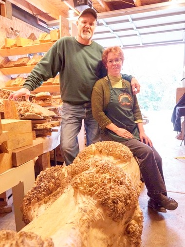 """Les Dougherty and wife Susan Curington are the owners of North Woods Figured Wood. Curington is sitting on """"Lucille"""" a maple burl log."""
