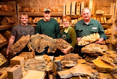 Les Dougherty and wife Susan Curington, owners of North Woods Figured Wood, stand between Mitch Graham (left) a Pacific University marketing intern and Mike Meredith, a master wood turner. Meredith will be demonstrating his skill at the open house July 13.