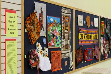 An educational display about fabric and fiber arts across the globe hangs in the children's area of the Forest Grove Library opposite a quilt created by the Chicas Youth Development program from Adelante Mujeres prior to a reception for the quilt on Sept. 23, 2014.