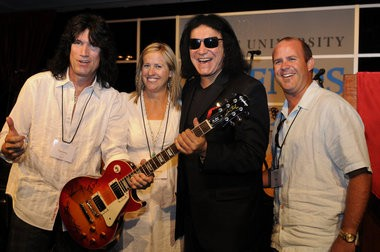 Tommy Thayer (left) and KISS legend Gene Simmons (third from left) pose with the successful bidders of a guitar signed the members of KISS at the 2010 Pacific University Legends Golf Classic.