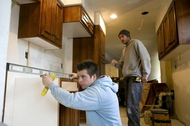 A remodeling crew installs new cabinets in a Portland kitchen project. Remodelers had fewer jobs in recent years, but last year's projects were bigger, and they report more interest early this year.