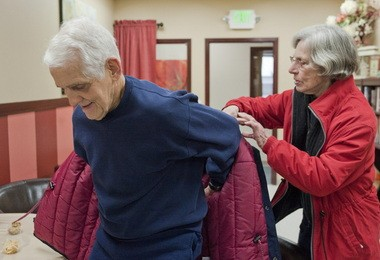 Gene Davidson, 81, of Gresham settles in for a visit to the Mount Hood Adult Day Center in Gresham with the help of his wife, Joan Davidson, 79.