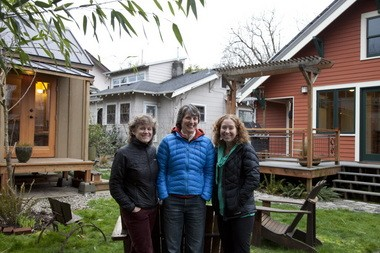 Friends (from left) Joan Grimm, Rita Haberman and Gina Bramucci gather outside Bramucci's tiny house in their shared backyard. The red house belongs to Grimm and Haberman, and the tan house is Lisa Pate's. The four friends formed a mini-community that comprises three households on two lots, sharing garden space, tools and camaraderie