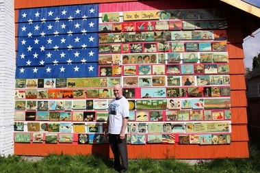 In this photo taken April, 2013, resident Richard Ormbrek stands next to his house, which has been decorated with a 20-foot wide American flag made up of 180 individually-painted tiles, in Seattle.