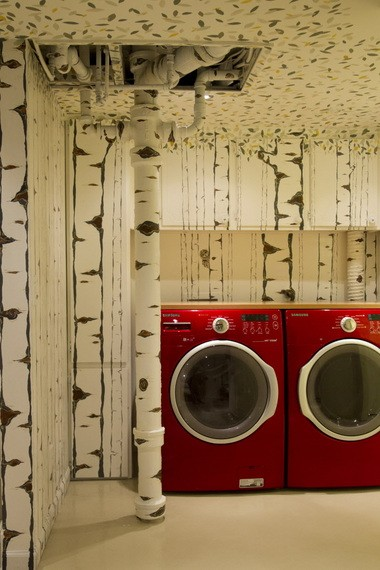 When faced with a vent stack they could not move, Patti Lavallee came up with the idea to celebrate it. The fire-engine red washer and dryer was on sale and added a pop of color to the basement space.