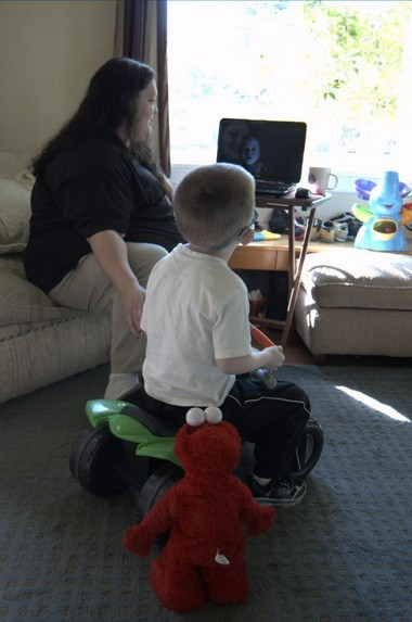 In the living room, 5-year-old Gavin Traum watches a video of his first word with his dad, Scott Traum, and Traum's girlfriend, Melissa Burke.