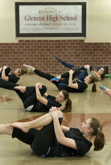 Members of the Glencoe High School varsity winter guard take an hour to stretch and warm up before practicing their routine for state competition.