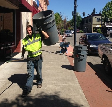 Daniel Brewer works to pick up yard debris in downtown Hillsboro on Friday. Brewer works for Jordan's Lawnscape & More LLC., which donated time and materials to spruce up downtown Hillsboro (Andrew Theen/The Argus).