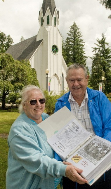 John and Judy Krug, standing in front of the Old Scotch Church, display one of the thick binders of family history on the Krug branch of their ancestry.