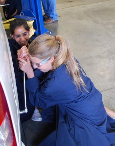 Maria Andrukhiv, 13, front and Leah Venkatesan, 13, team up to pry loose bolts holding a car wheel in place, during the Girls Get IT tech camp at Hillsboro High School. Andrukhiv is visiting from New Hampshire and Venkatesan attends St. Matthew Catholic School in Hillsboro.