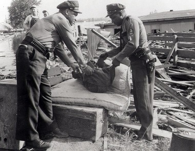 Deputy sheriffs Matt Dishman and William Travis place the shrouded body of 11-month-old Sally Butcher on mattress to await arrival of coroner. Her body, and that of her brother, Michael, age 2, were the first to be recovered from the wreckage-strewn waters of Vanport. They were found on Friday, June 4, 1948.