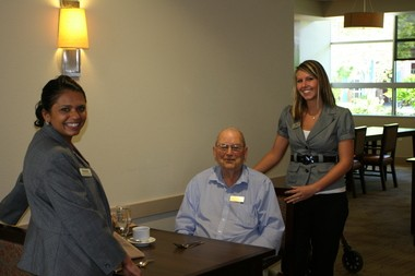 Russellville Park General Manager Meghna Davidson and Health and Wellness Coordinator Sara Albers greet resident Bob Peterson at lunchtime.