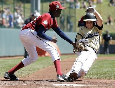 In a moment sure to be a nail-biter for any watching parent, Gresham's Hunter Hemenway tries to score on a wild pitch in a consolation game at the 2012 Little League World Series but is tagged out by Uganda's Daniel Alio.