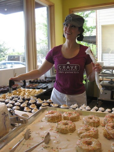 """Kyra Bussanich, owner of Crave Bake Shop in Lake Oswego, talks with customers while flaming the marshmallow creme tops of a batch of """"hot chocolate cupcakes."""" The bakery filed a complaint last week in federal court against a similarly named gluten-free bakery in San Francisco in an effort to stop repeated threats to sue for trademark infringement."""