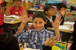 Uriel Salinas puts his hands up and shakes them with the rest of the class at Echo Shaw Elementary School. This is the symbol for a word that is a cognate -- common etymological origin -- kind of like a free word that is the same in Spanish or English. Estella Weigand's 4th grade class does their work in English in the morning and in Spanish in the afternoon. Benjamin Brink/Staff Photographer