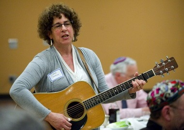 Emily Gottfried leads a song during a community Passover Seder in 2011. A tireless organizer and worker in Jewish and interfaith circles, she died Jan. 27 at age 57.
