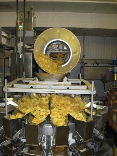 After being coated with powdered flavoring in a large spinning drum, chips are dropped into recepticles where they are portioned by weight.