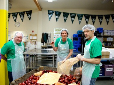 (left to right) Comcast employee volunteers Gary Yates and Kathy McGowan, with Hands On Greater Portland volunteer Mark Vanderyacht, bag apples at the Oregon Food Bank volunteer action center.