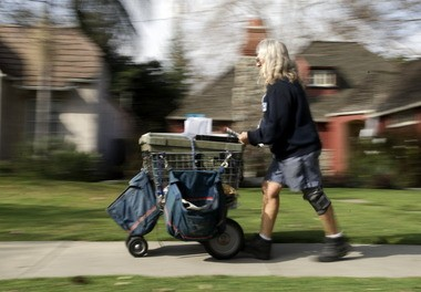 A mail carrier walks her route in Santa Ana, Calif. on Wednesday as the Postal Service announces plans to end Saturday mail delivery.