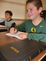 Alex Bovhduga, (foreground) 12, a Rowe Middle School student, and Paul Simchuk, 11, an Estacada Web Academy student, are learning to write literary passages and Bible verses in Ukrainian. A Ukrainian language Bible is on Alex's desk.