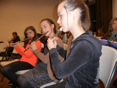 Playing flutes in a youth orchestra are, from foreground, Anastasiya Tishkova, Irina Tishkova and Julia Zavgorodniy. In background is violinist Stephan Kaidan. The orchestra is practicing a medley of Christmas carols for a Dec. 14 program at a Ukrainian church in Milwaukie.