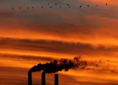 A flock of geese fly past the smokestacks at the Jeffrey Energy Center coal power plant near Emmett, Kan.