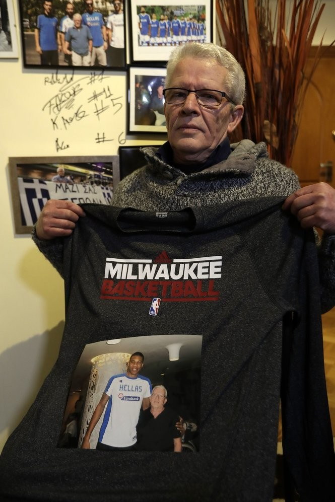 In this Tuesday, Feb. 7, 2017, photo, Giannis Tzikas, a cafe owner in Athens, Greece, and neighbor of the Antetokounmpos, poses with a photo and a T-shirt of Giannis Antetokounmpo in front of the wall with his autograph.