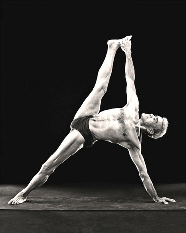 Dharma Mittra poses in Vasisthasana, a variation of the side plank.