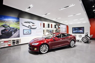 Automobile manufacturers worry that a proposed road-usage charge on fuel-efficient vehicles could discourage purchase of vehicles such as the electric Tesla.
