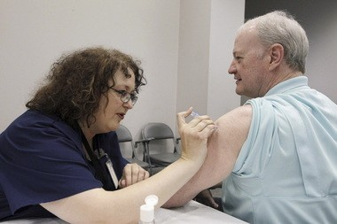 In this file photo taken last fall, Bill Staples, a Mississippi Department of Health employee, is given a shot of flu vaccine in Jackson, Miss. A survey by Centers for Disease Control and Prevention researchers found that in 2011, more than 400 U.S. hospitals required flu vaccinations for their employees and 29 hospitals fired employees that were not vaccinated against the virus. Research suggests that vaccinating health care workers may provide important protections for elderly and medically fragile patients.