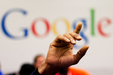 In this Oct. 17, 2012, file photo, a man raises his hand at the Google offices.