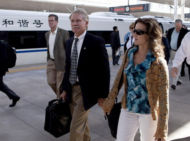 Gov. John Kitzhaber and companion Cylvia Hayes walk beside the high-speed train as they arrive visit to Tianjin, China, Sept. 20, 2011.