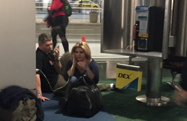 Dan Luna, working in the information booth in the baggage claim area at Portland International Airport on Wednesday night, Feb. 10, 2016, said he heard a man and woman yelling that they needed to speak with the FBI. Luna helped them them find an electrical outlet to power their phones and quickly realized it was related to the Malheur National Wildlife Refuge takeover. On the floor of the terminal, Mike Arnold, Ammon Bundy's lawyer and Nevada Assemblywoman Michele Fiore. (Courtesy of Dan Luna)