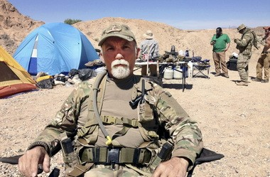 In this April 16, 2014, file photo, Jerry DeLemus, of Rochester, N.H., sits with a group of self-described militia members camping on rancher Cliven Bundy's ranch near Bunkerville, Nev. Federal agents arrested DeLemus Thursday, March 3, 2016, in New Hampshire. He faces multiple federal charges in Nevada.