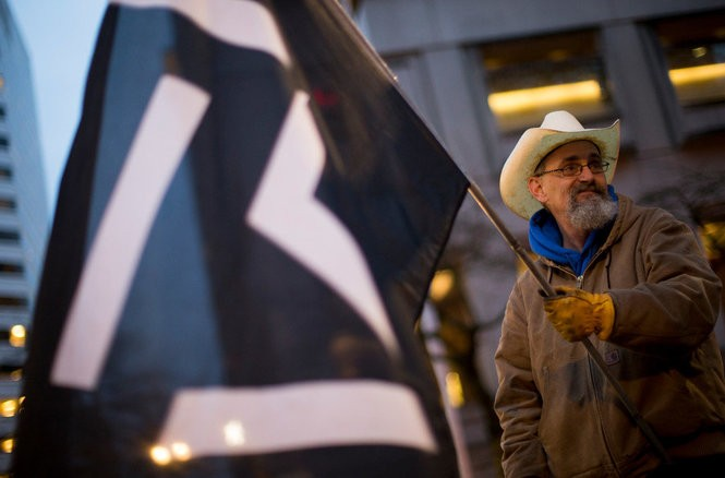 "Chris Border of Milwaukie stands at the corner of Southwest Third Avenue and Main Street in downtown Portland and waves a flag with a symbol that represents Robert ""LaVoy"" Finicum on the two-year anniversary of Finicum's death."